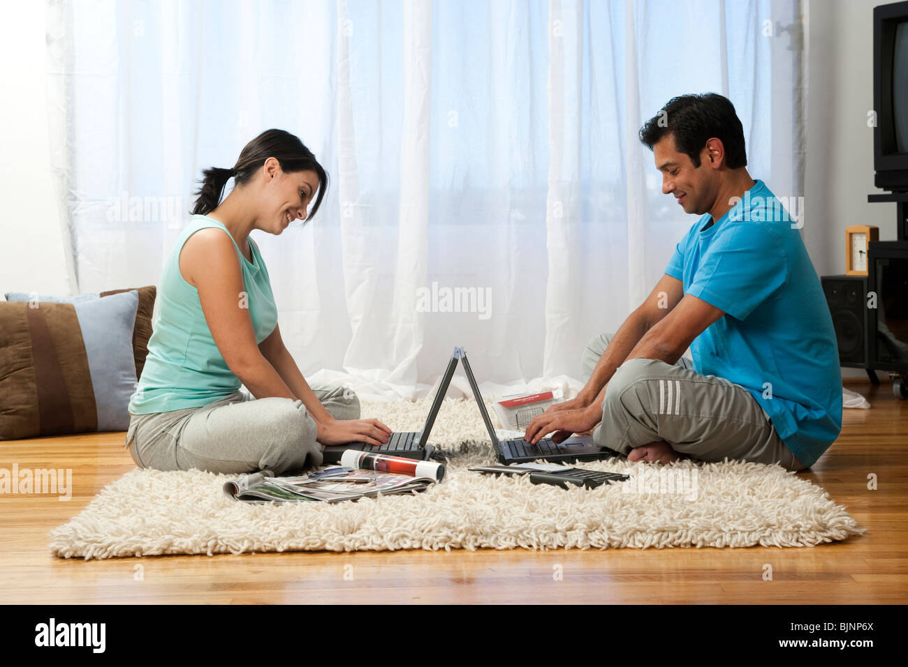 Man and woman lying on carpet with laptops - Stock Image