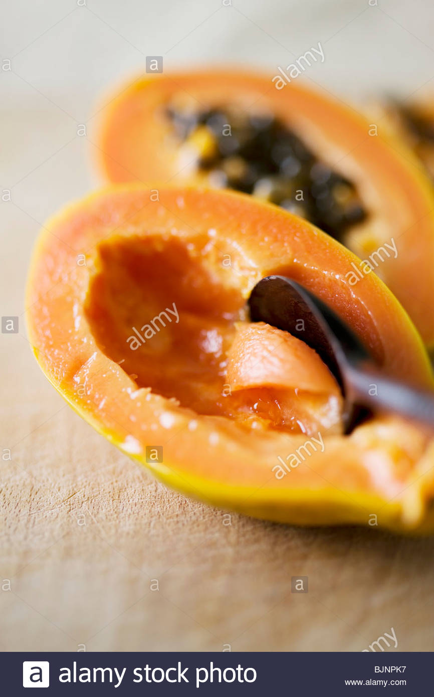 Hollowing out a papaya with a spoon - Stock Image
