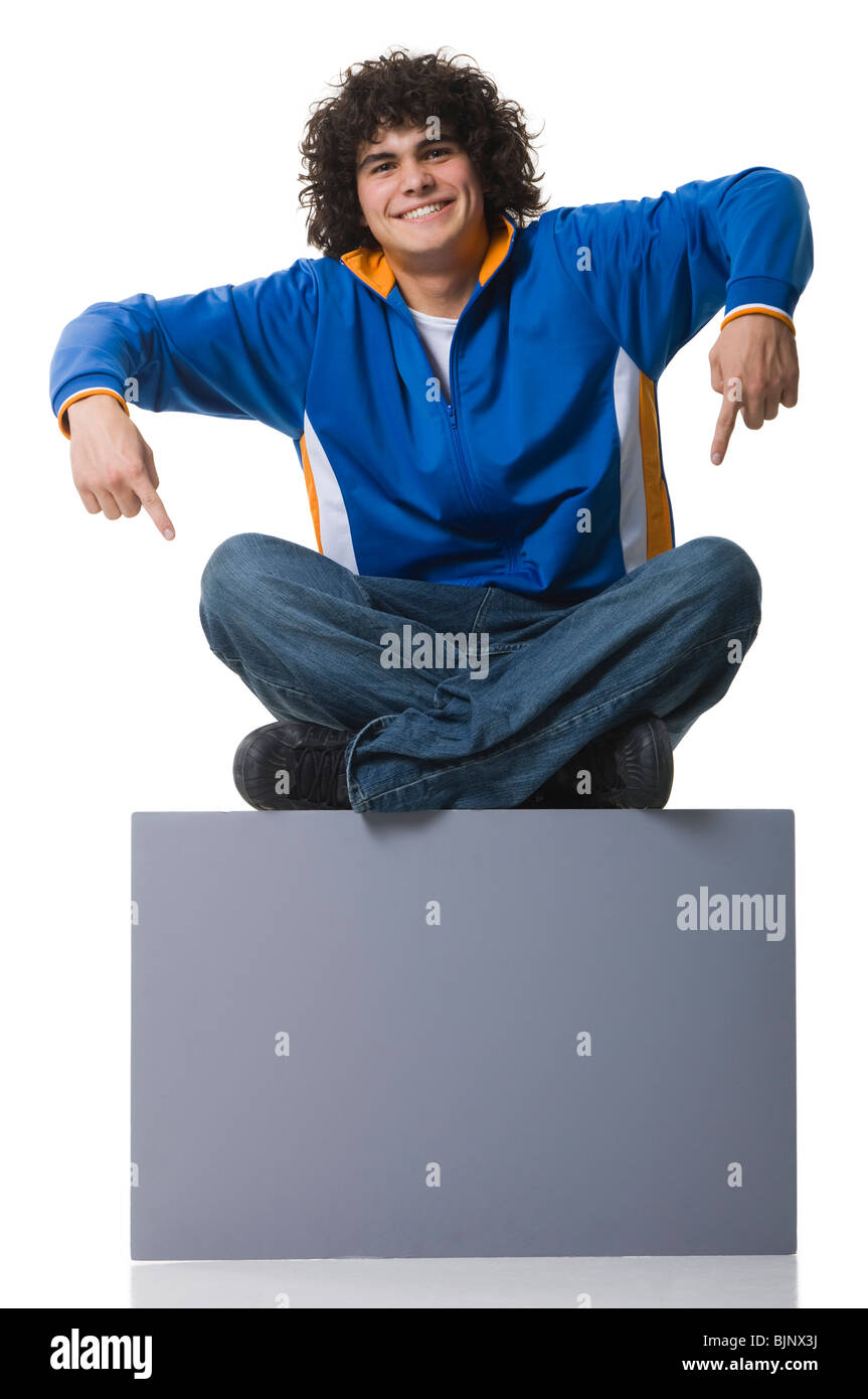 Man sitting on blank sign - Stock Image