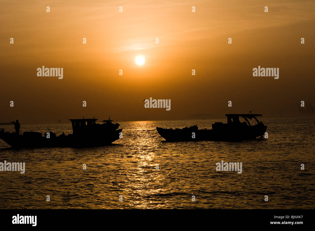 Fishing  boats during sunset in the south China sea. - Stock Image