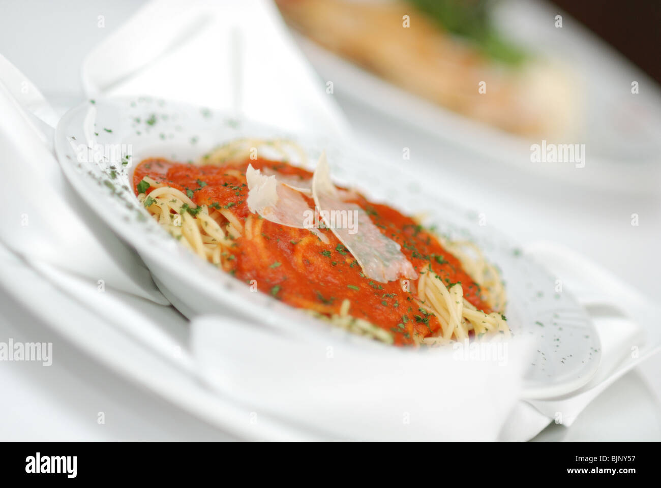 Pasta served at restaurant with tomato sauce and parmesan - Stock Image