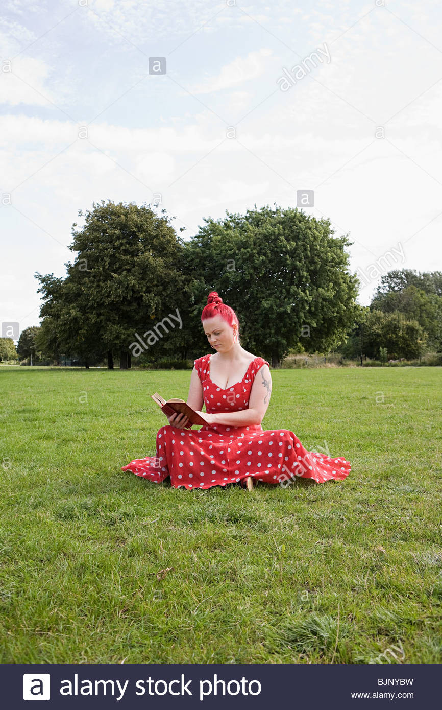 Woman reading a book in a field - Stock Image