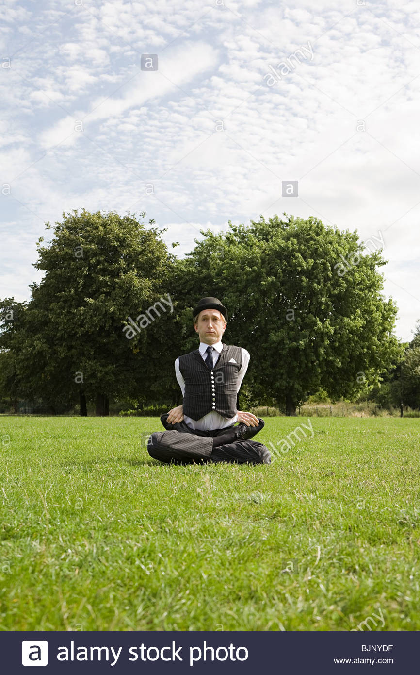 Contortionist sitting in a field - Stock Image