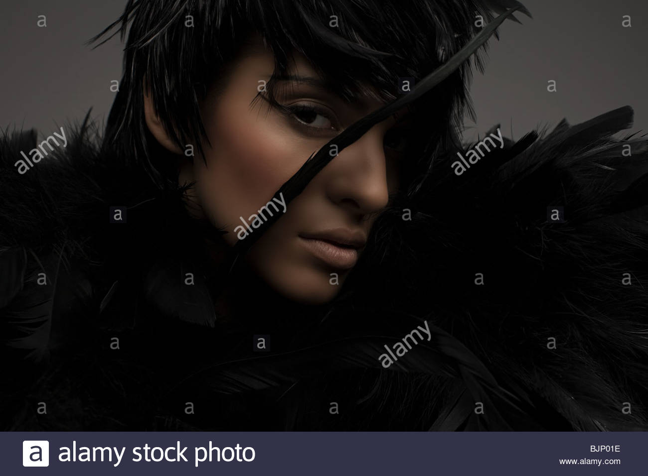 A woman wearing a feather headdress - Stock Image