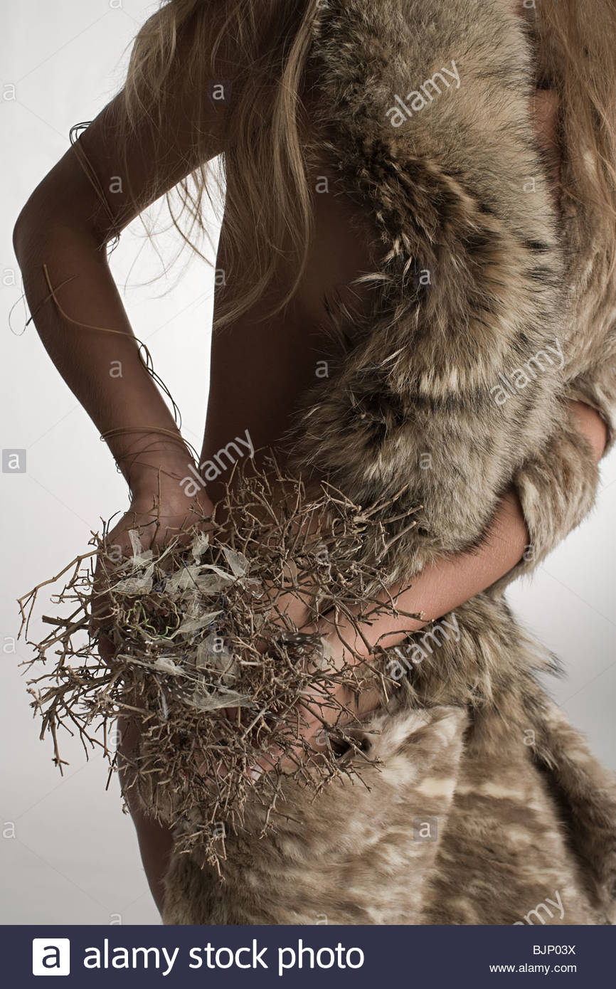 A woman holding twigs - Stock Image
