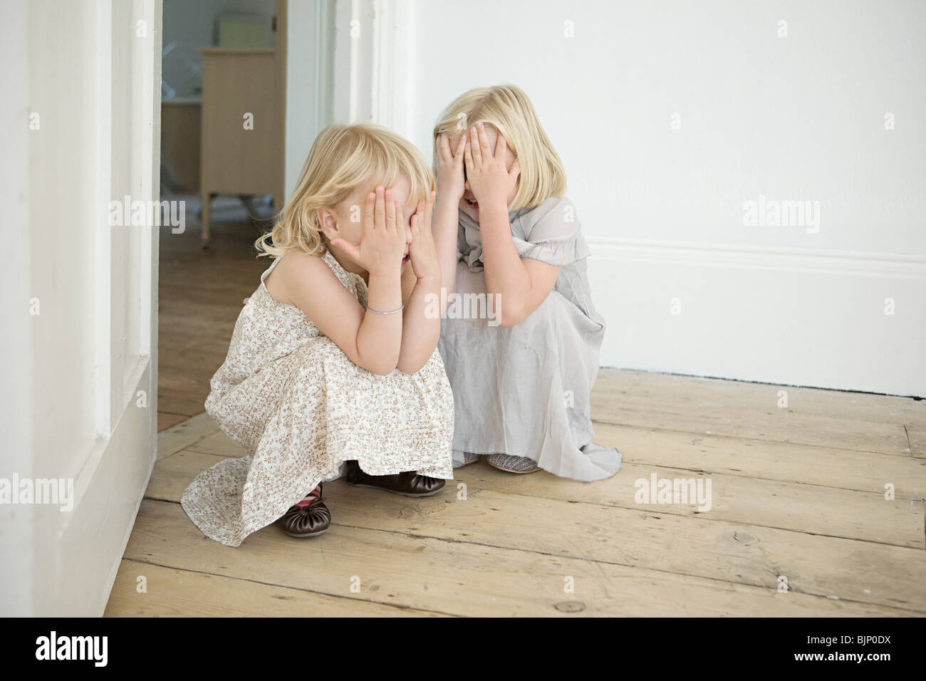 Sisters playing hide and seek Stock Photo