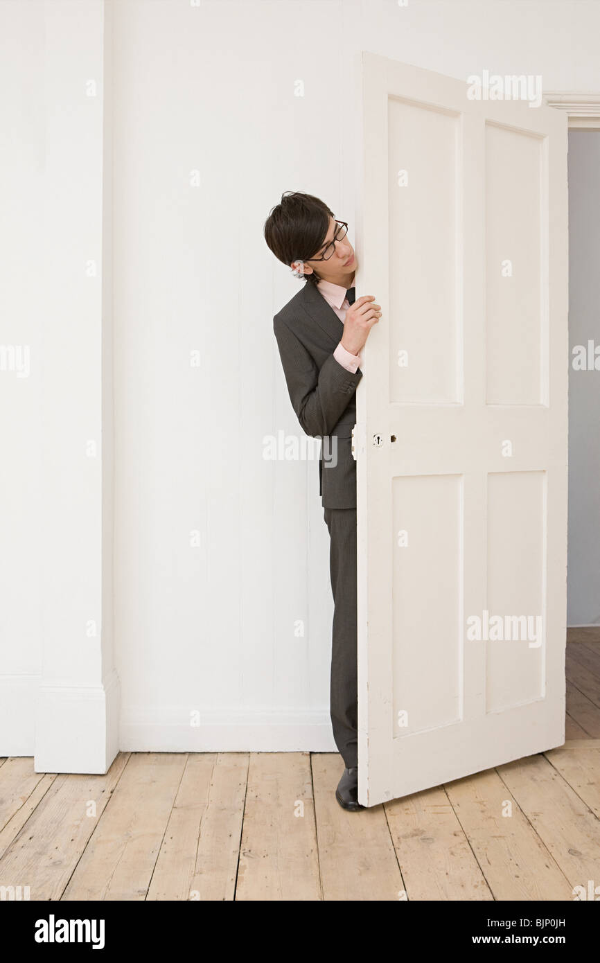 Businessman hiding behind a door - Stock Image