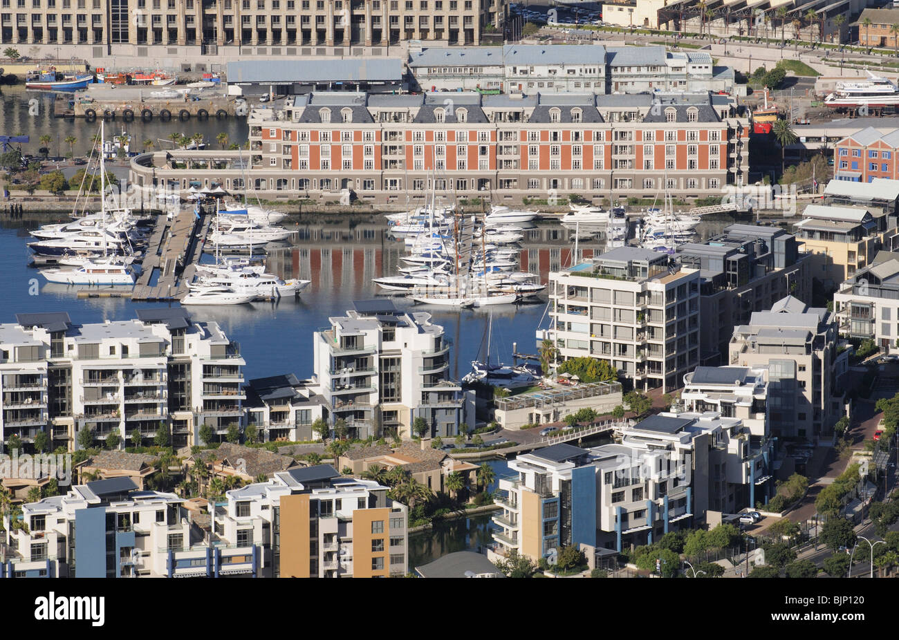 The red brick building is the Cape Grace a luxury hotel surrounded by a marina and residential housing on the V&A - Stock Image