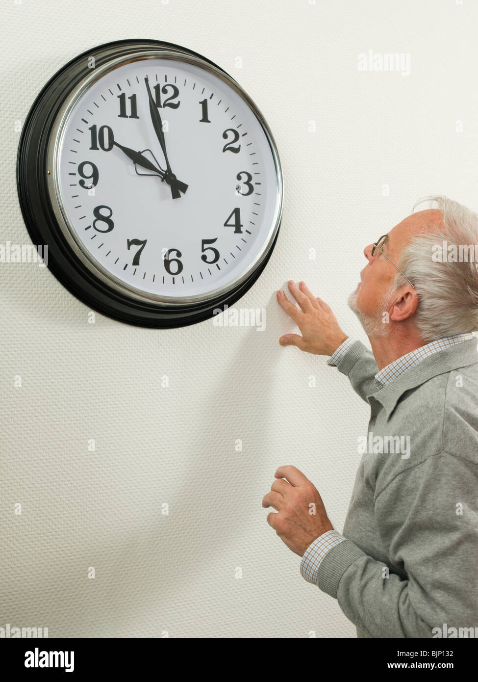 senior man looking at a large clock stock photo 28757990 alamy