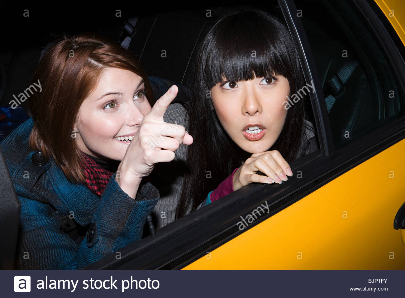 Girlfriends in a taxicab - Stock Image