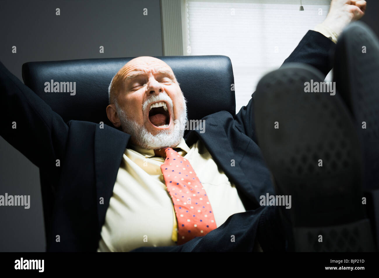 Closeup of businessman yawning in office - Stock Image
