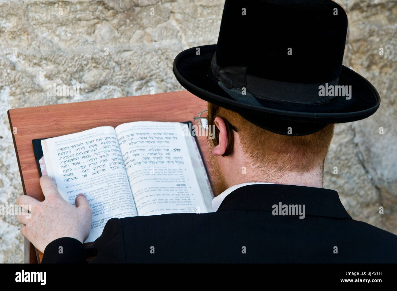 Studying the bible by the wailing wall. - Stock Image