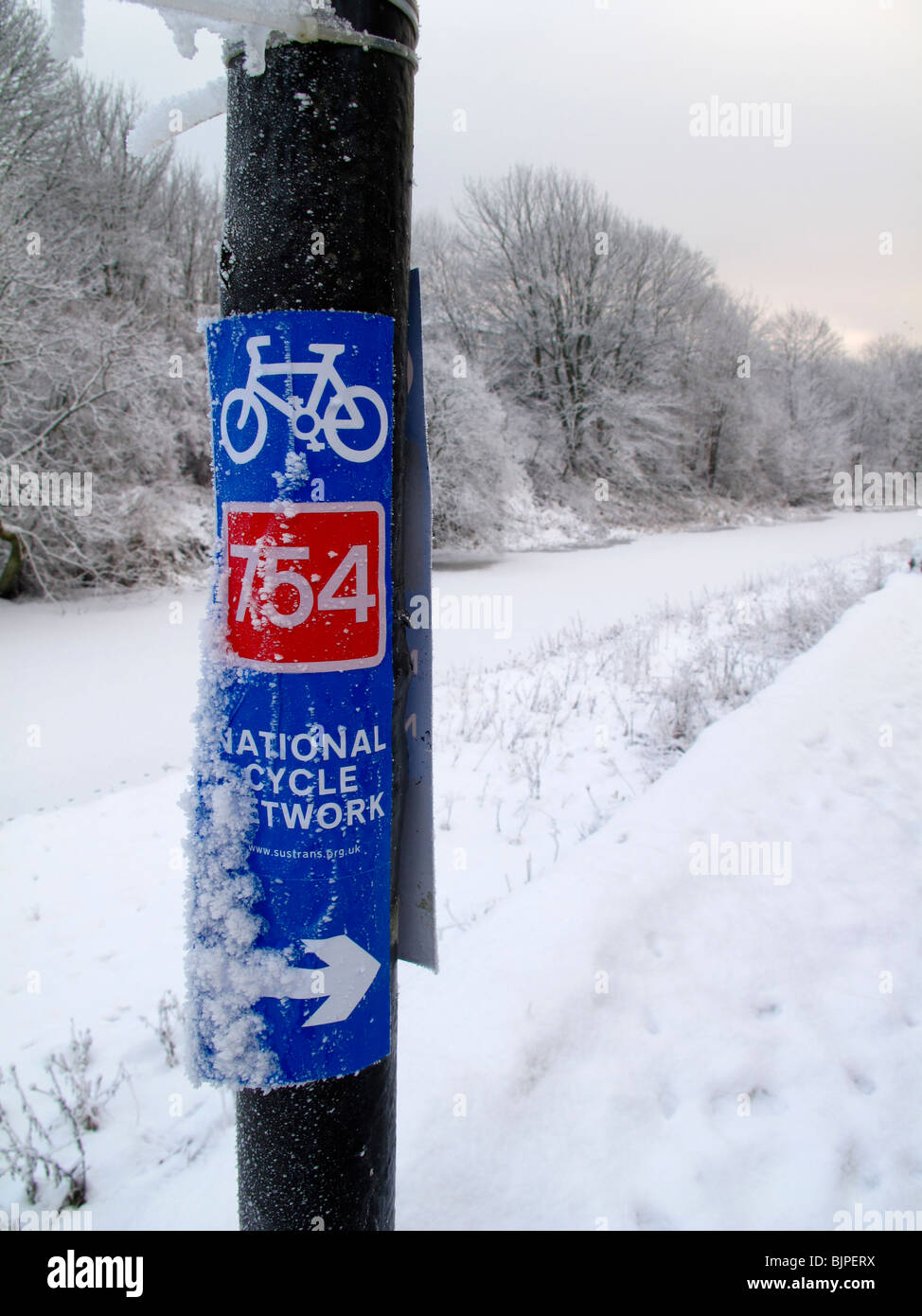 Cycleway signpost by canal in winter - Stock Image