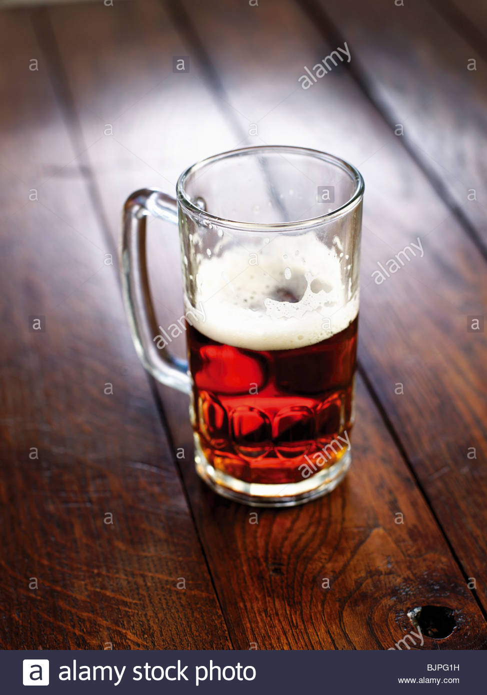 Half-full glass of beer on wooden background - Stock Image