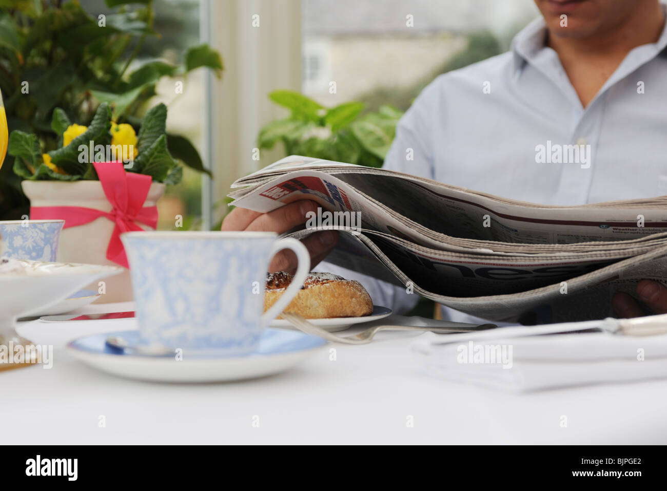man reading paper with continental breakfast - Stock Image