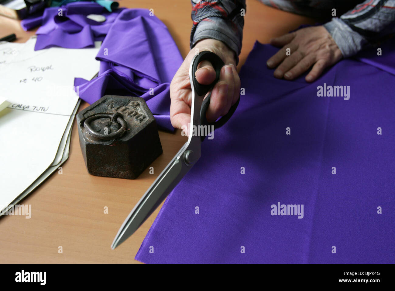 Woman`s hand cutting fabric with a scissor. - Stock Image
