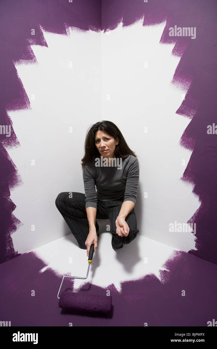 Woman painting herself into a corner - Stock Image