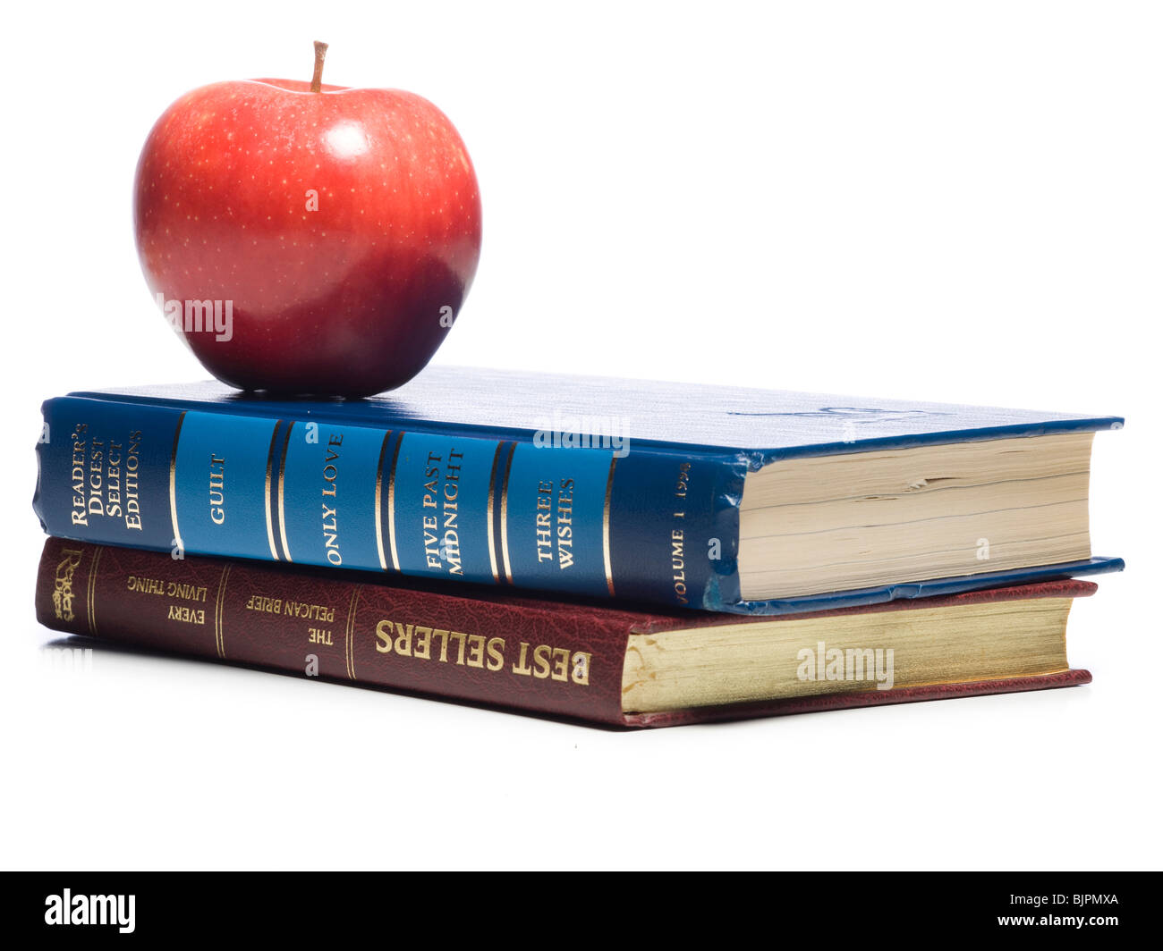 Two books with a red apple - Stock Image