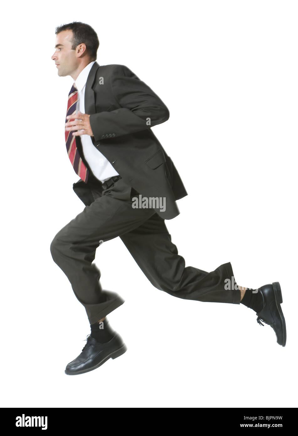 Man running in three piece suit - Stock Image
