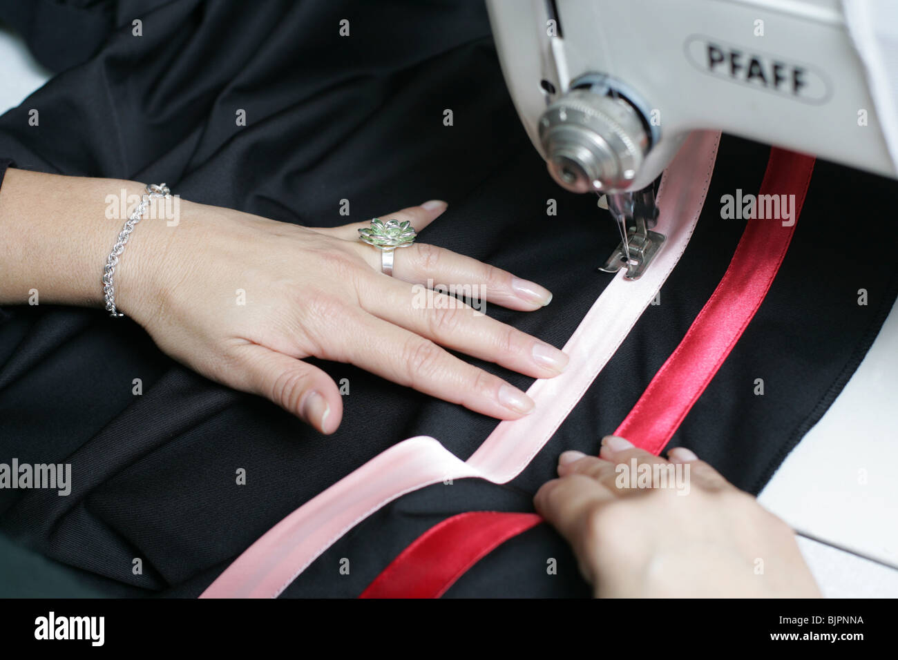 Woman working on a sewing machine. - Stock Image