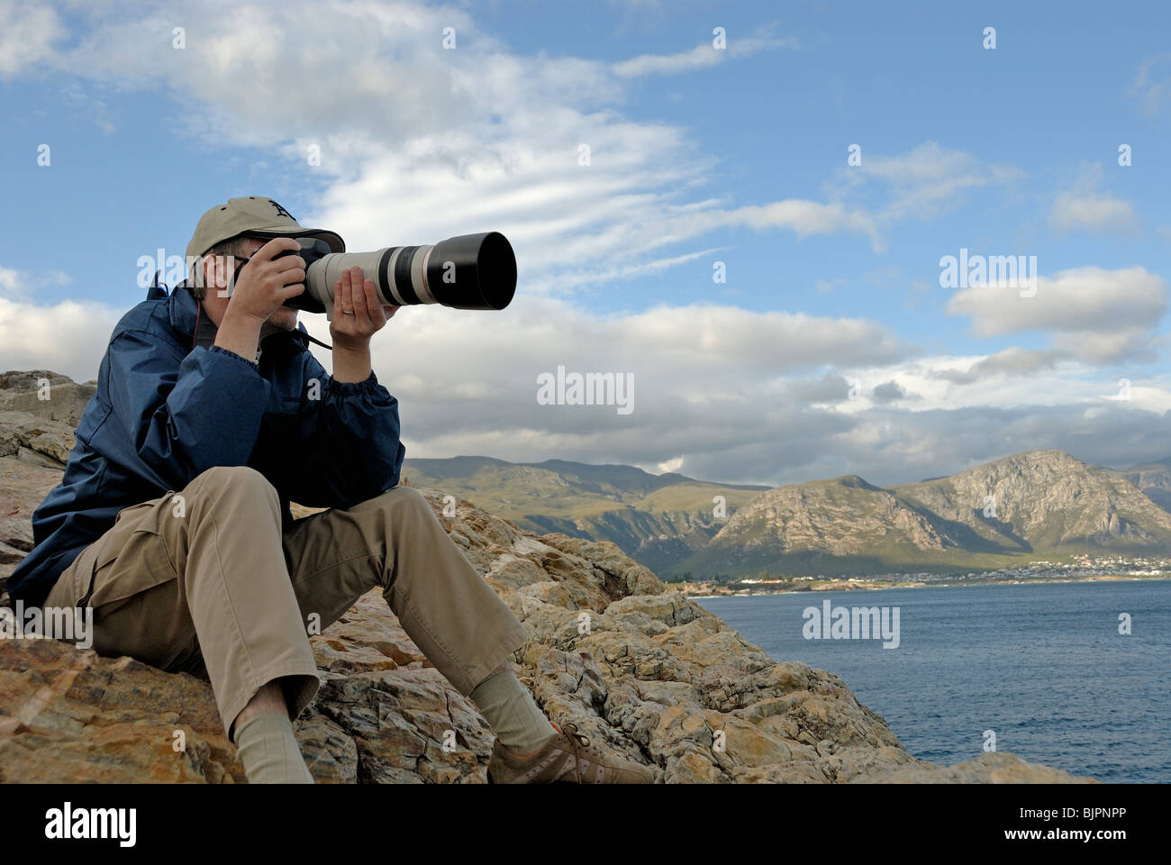 Man photographer taking a photograph of a landscape with telephoto lens, South Western Cape, South Africa - Stock Image