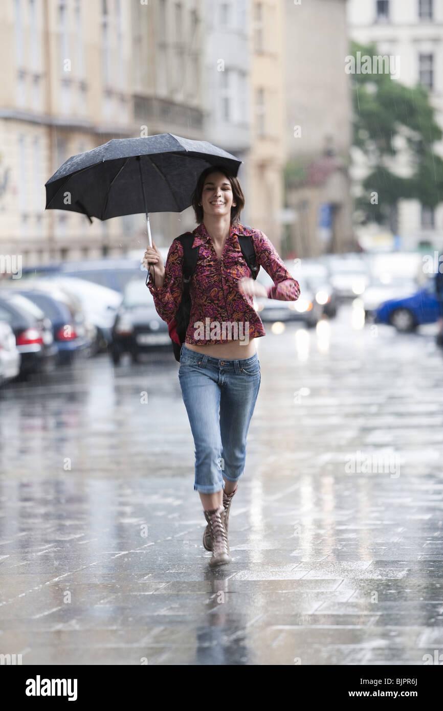 Woman walking down the street in the rain - Stock Image