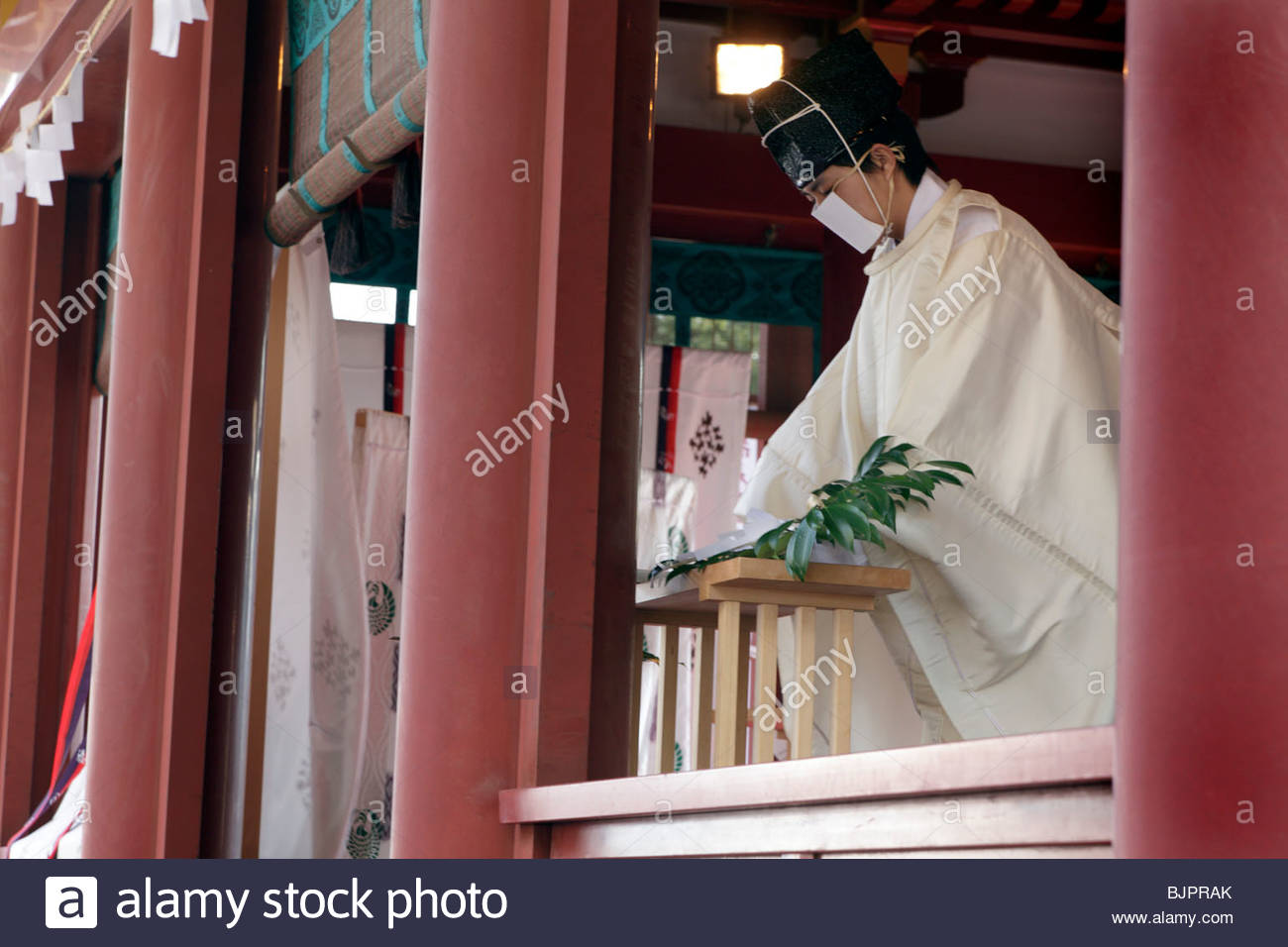 Shinto priest giving prayers during New Years celebration at the Tsurugaoka Hachimangu shrine in Kamakura - Stock Image