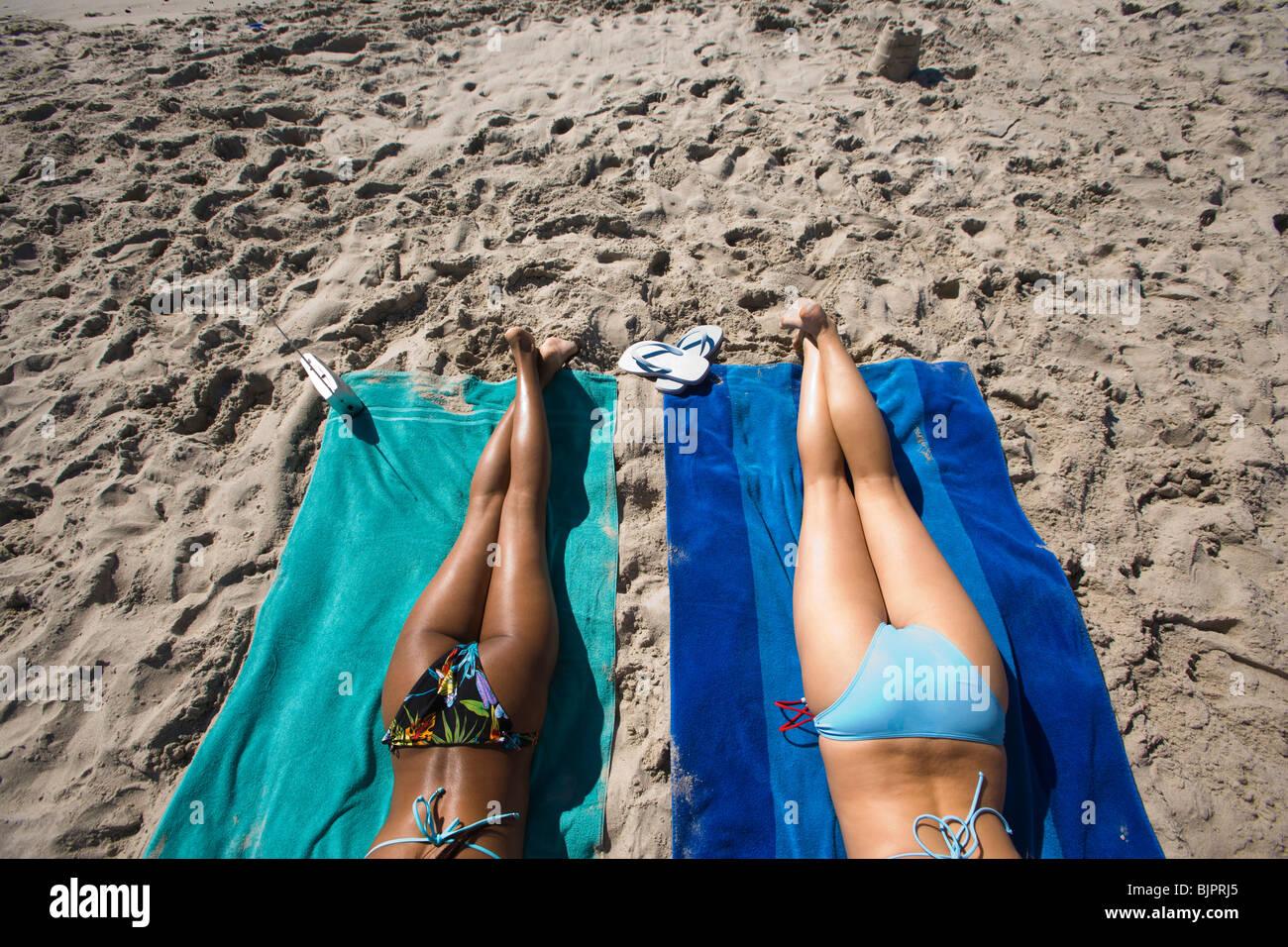 Legs of two women sunbathing at the beach - Stock Image