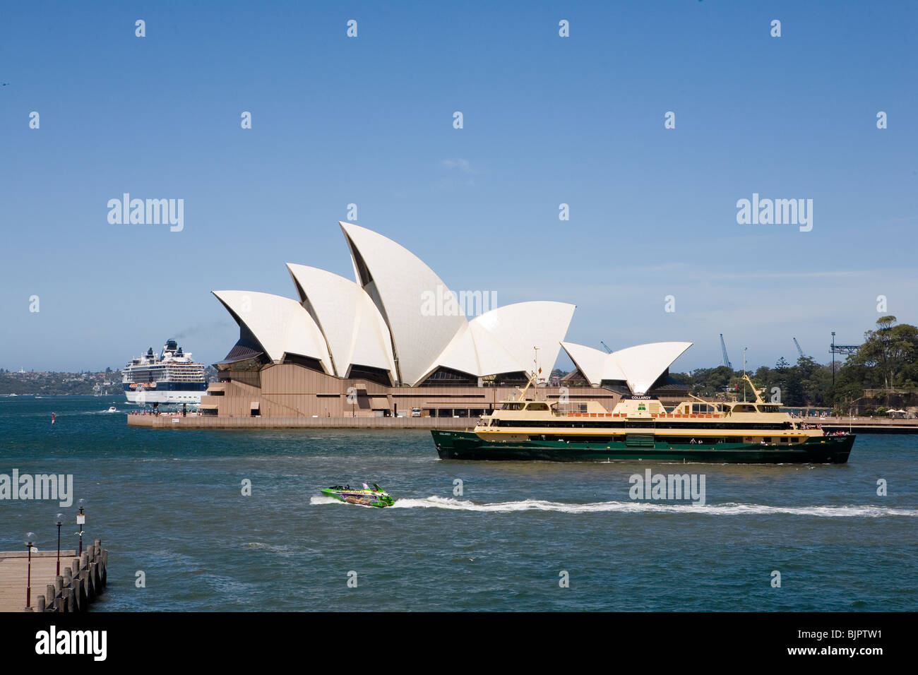 Sydney Opera House with ferry in the foreground and a cruise ship leaving in the background - Stock Image
