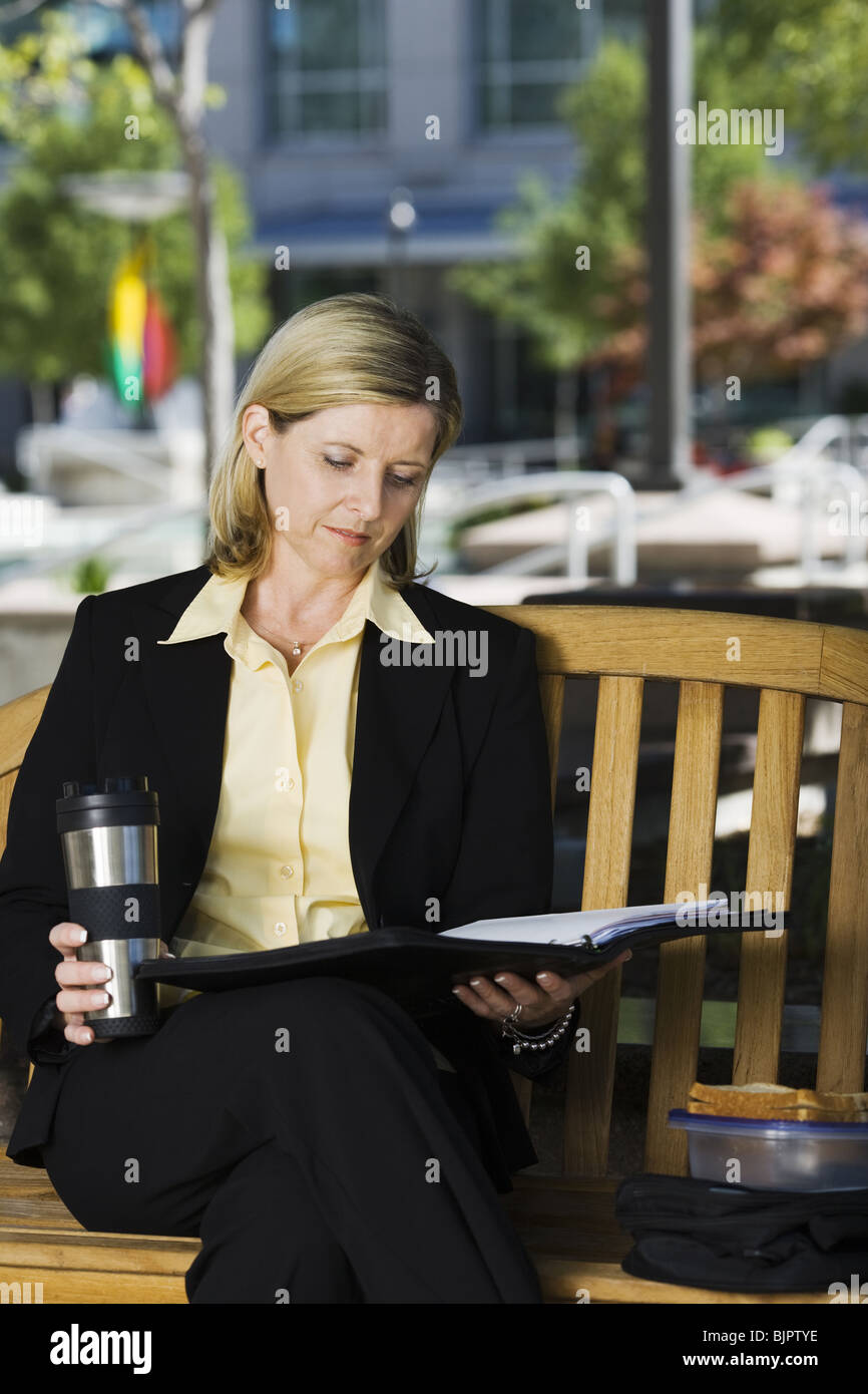 Businesswoman reading on park bench - Stock Image