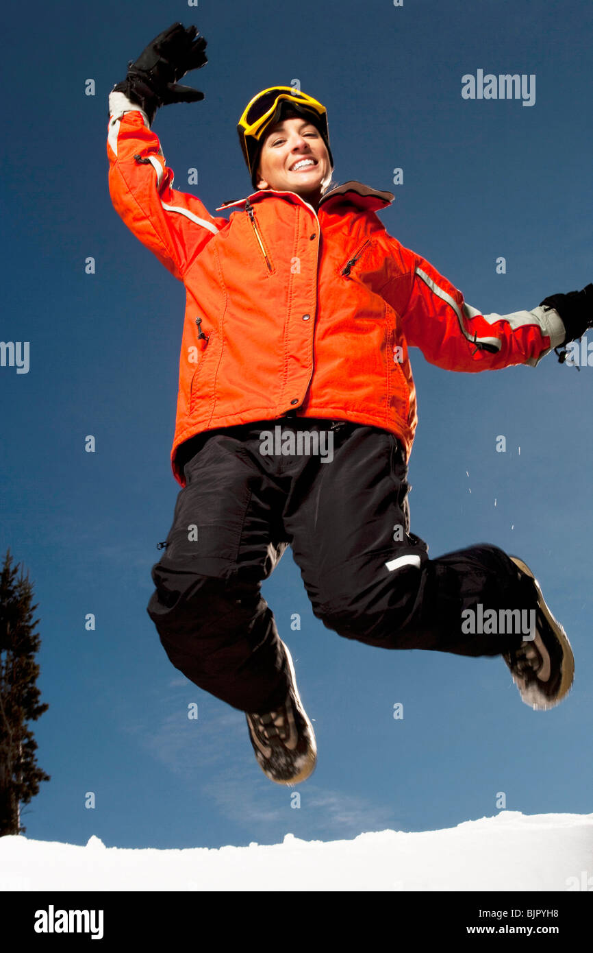 Woman jumping outside in the snow - Stock Image