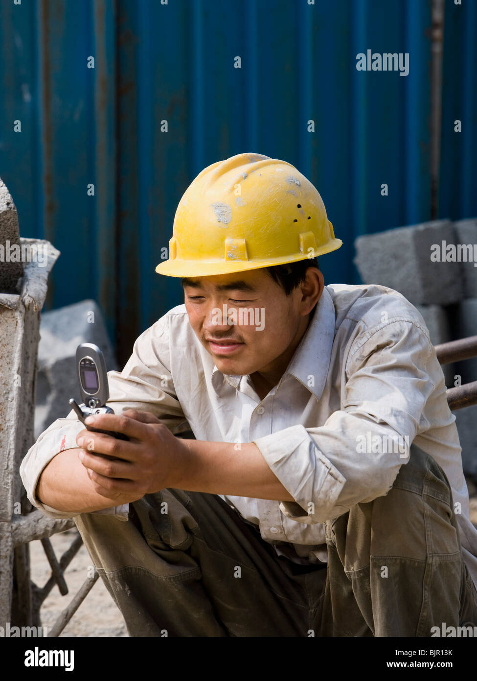 Construction worker looking at his cell phone. - Stock Image