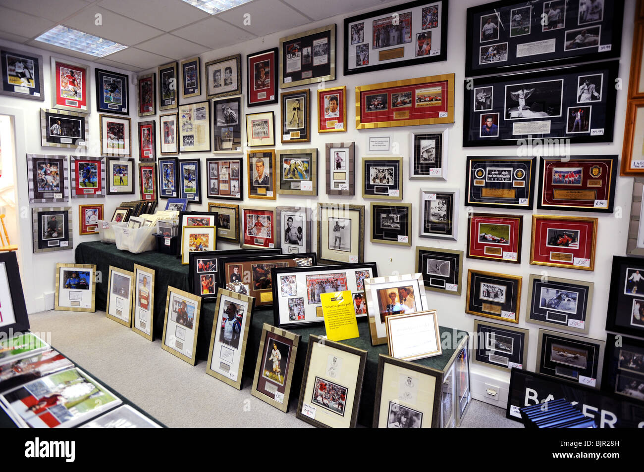 Autographed photo's and memorabilia hang in a shop in Haywards heath - Stock Image