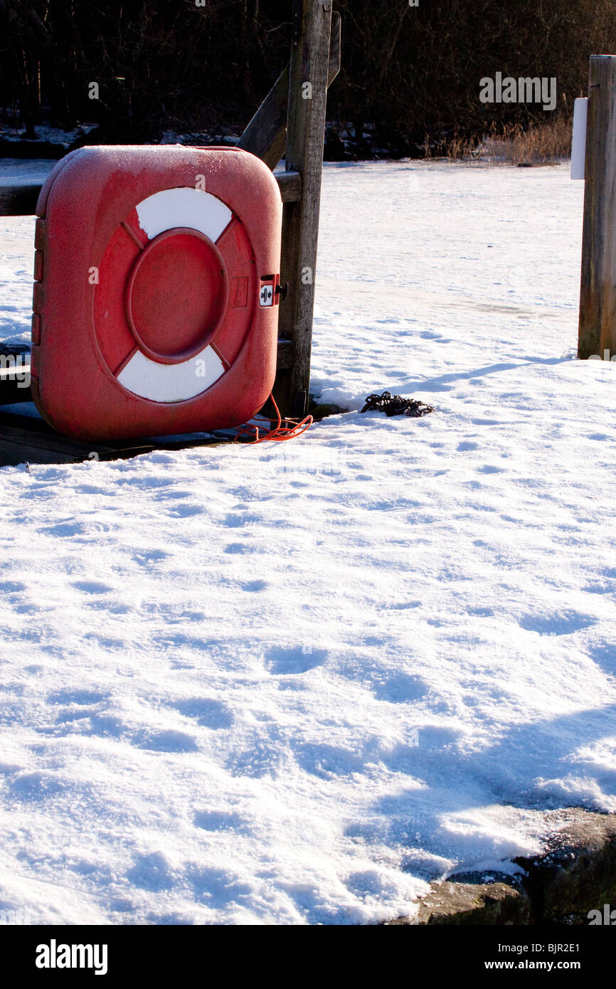 Lifebelt on snow covered jetty - Stock Image