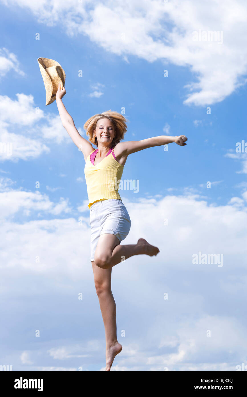 Woman jumping with a cowboy hat - Stock Image