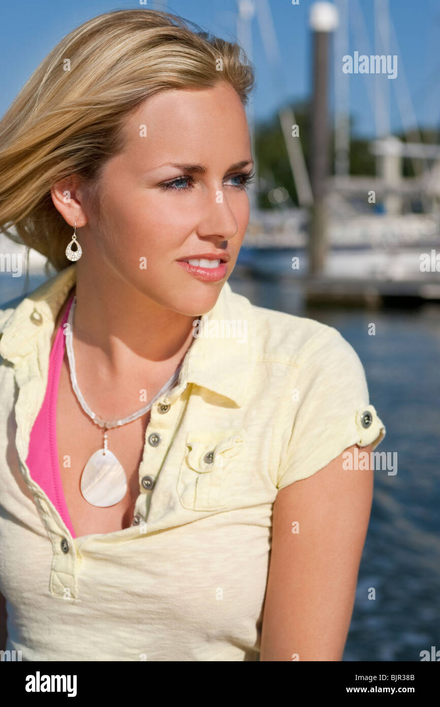 Portrait of a beautiful young blond woman sitting by the sea in glorious summer sunshine - Stock Image