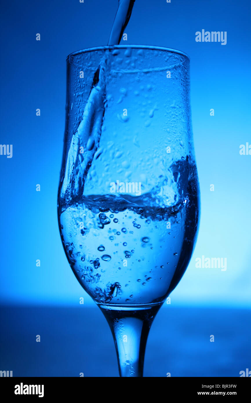 Glass with water on blue background. - Stock Image