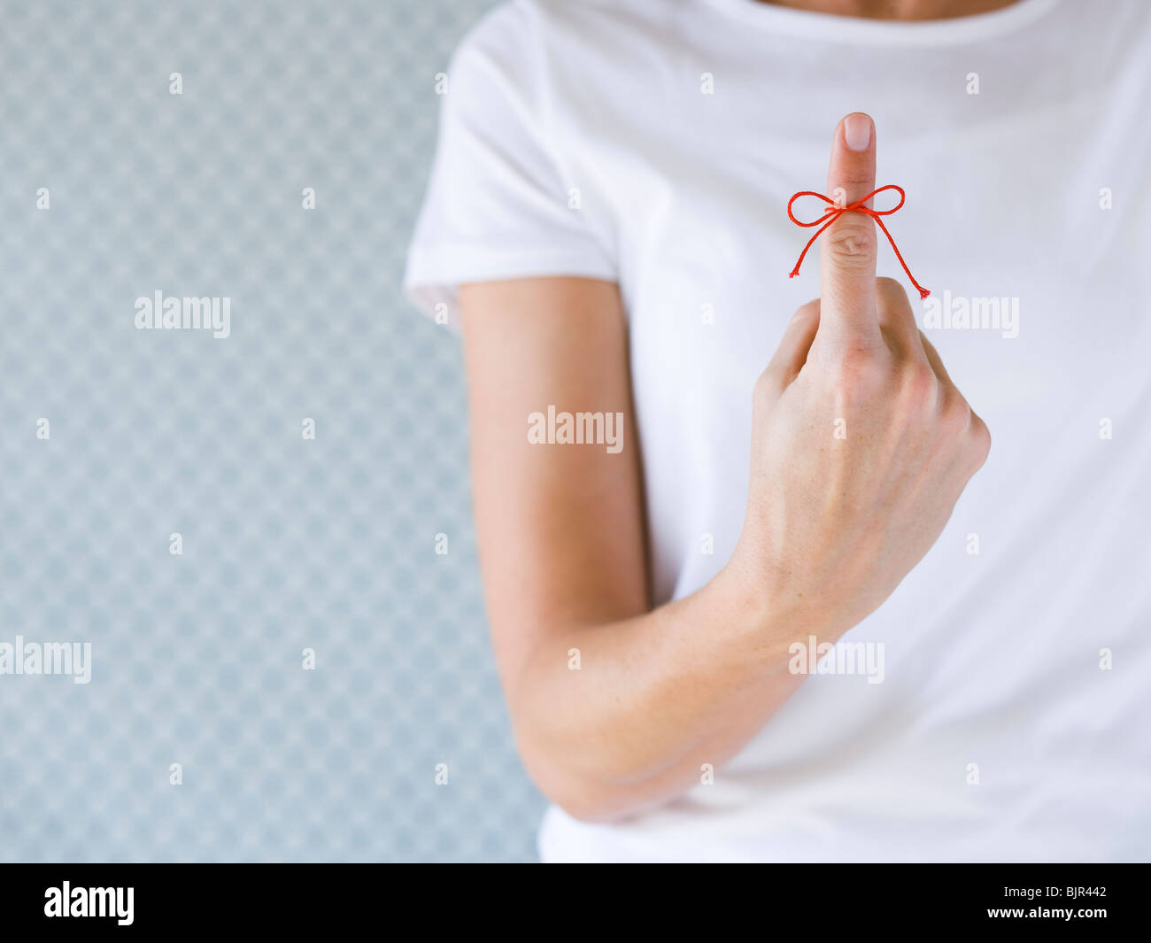 Woman with a red string tied on her finger. - Stock Image