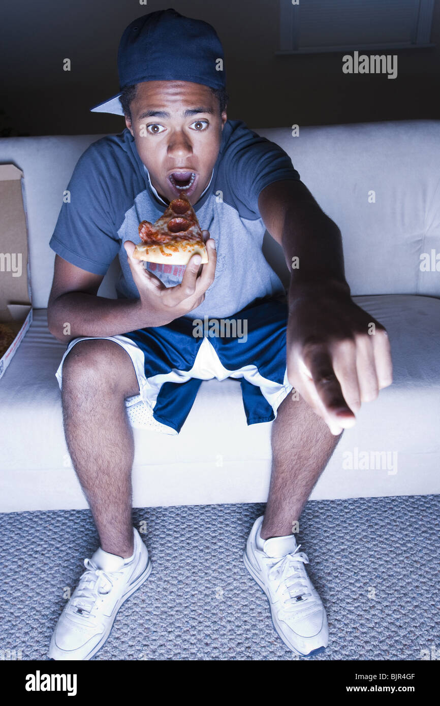 Teenage boy eating popcorn and pointing his finger - Stock Image