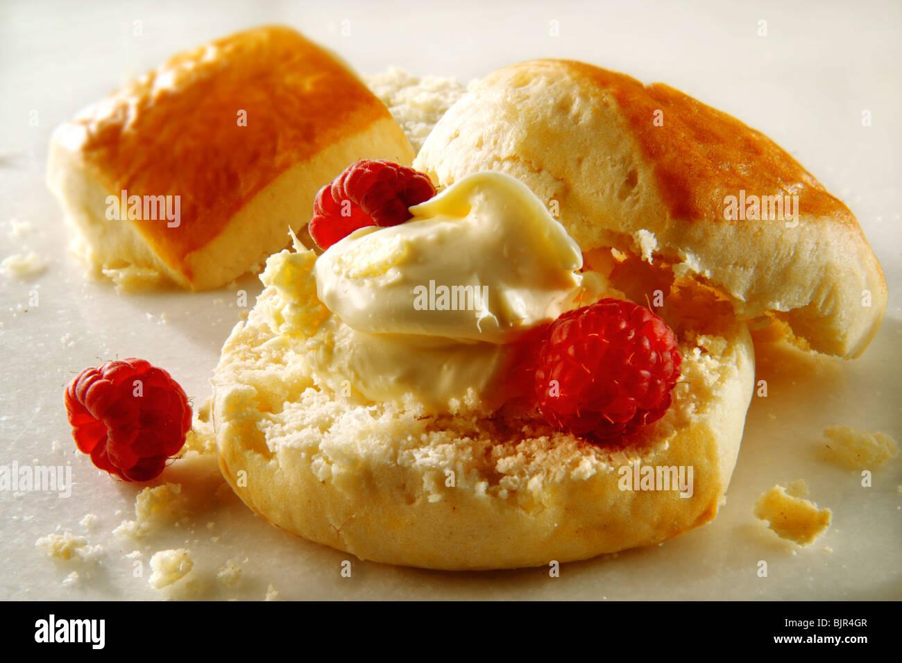 Traditional British sweet scones, clotted cream and fresh raspberries - Stock Image
