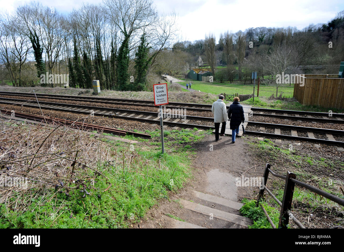 A couple walk over the railway lines at a quiet crossing point in the country - Stock Image