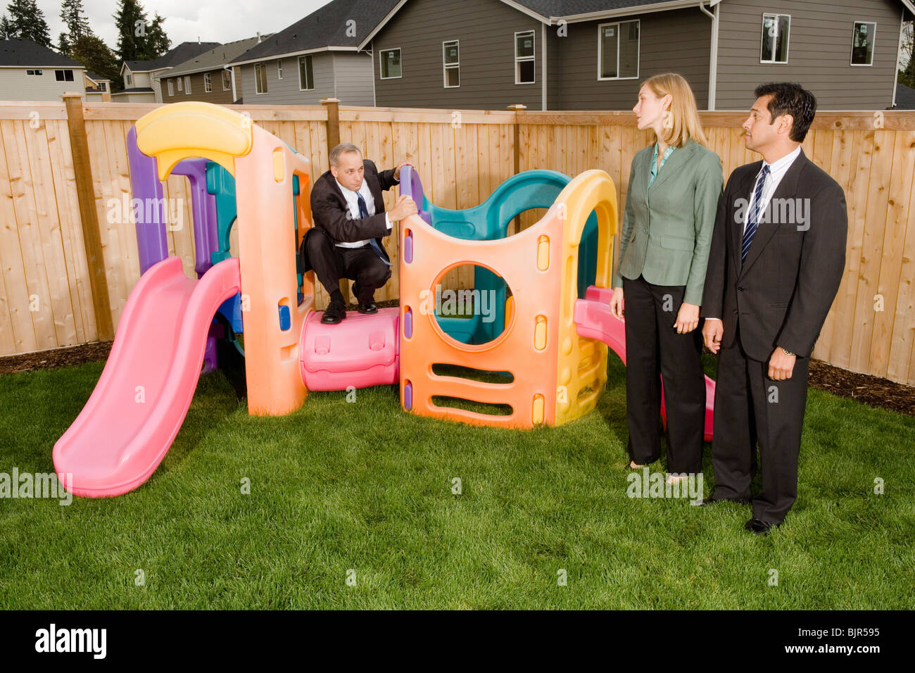 Three businesspeople playing on a jungle gym - Stock Image