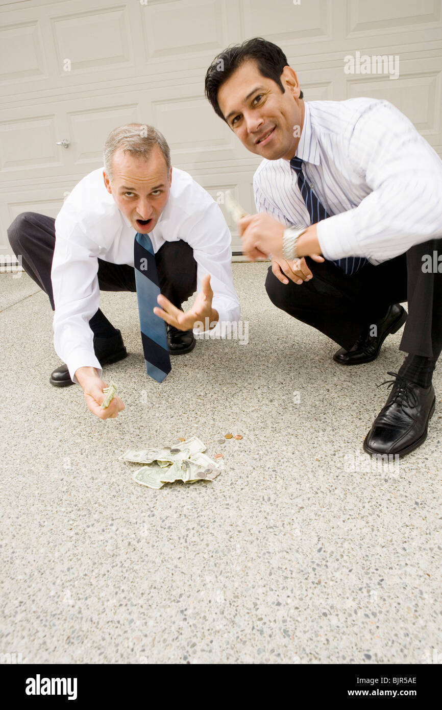Two businessmen gambling on a driveway - Stock Image