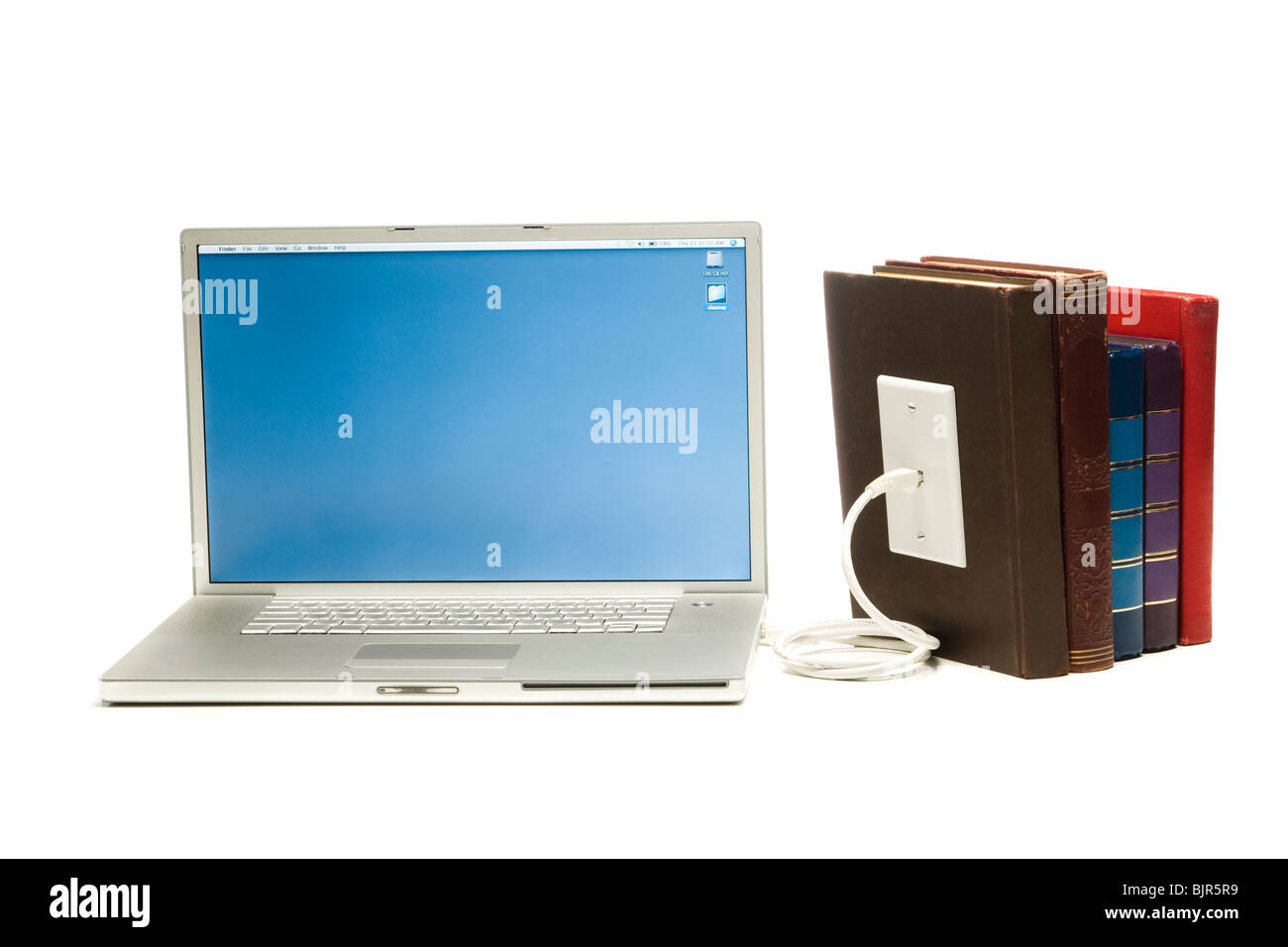 notebook computer plugged into books - Stock Image