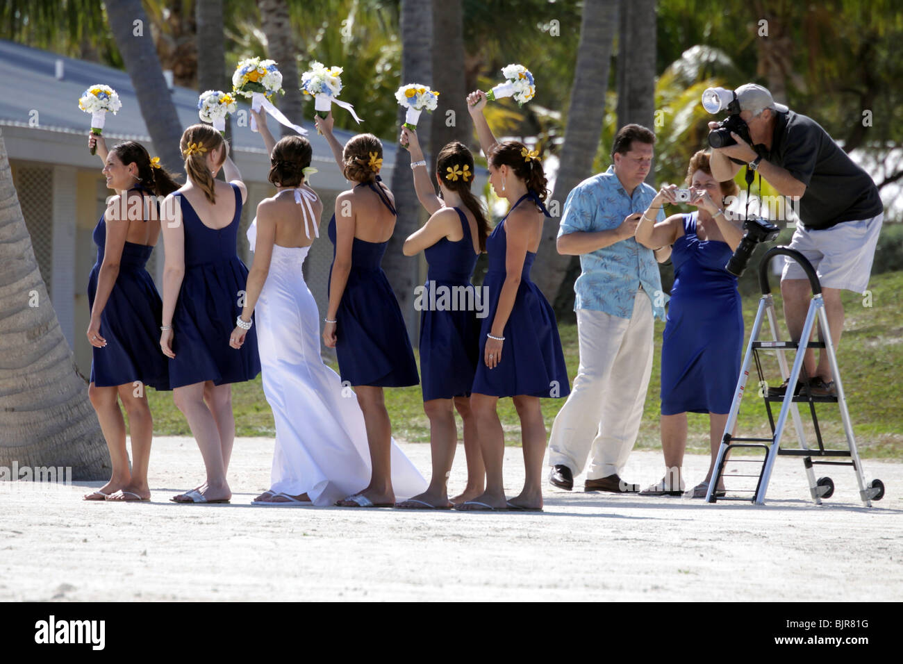 Bride And Bridesmaids Pose For Wedding Photos On The Beach With