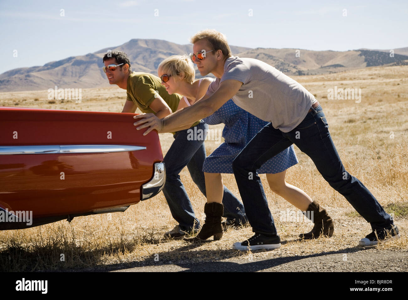 people pushing a car down the road - Stock Image
