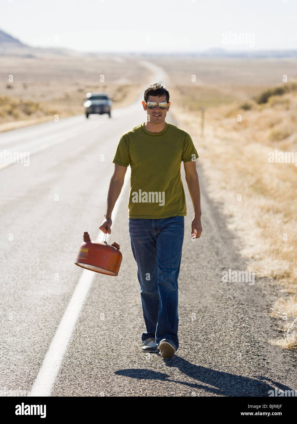 man walking with a gas can - Stock Image
