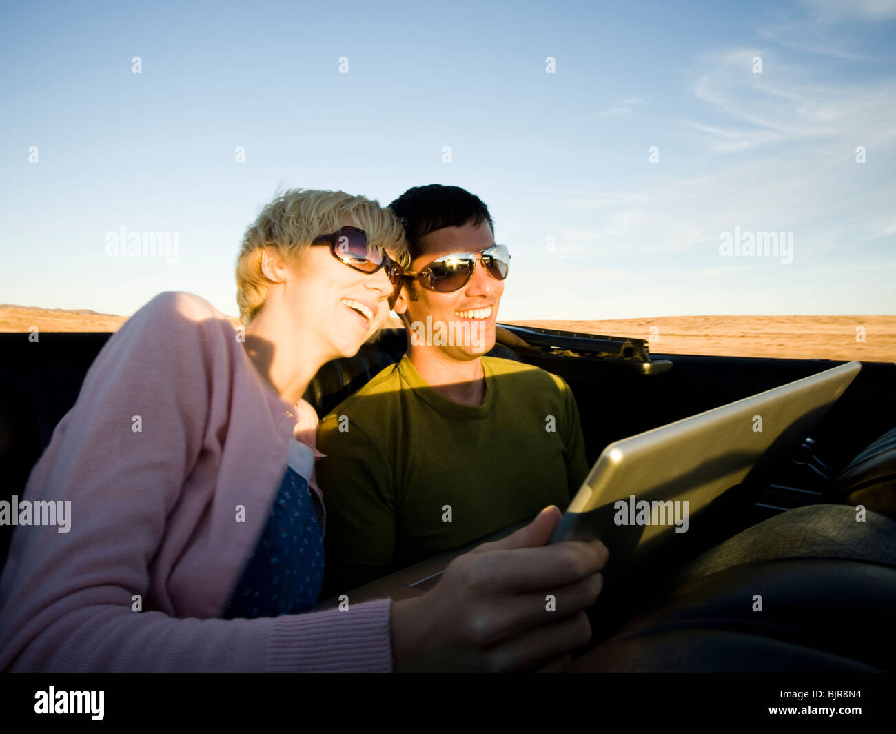 man and woman next to a red convertible - Stock Image