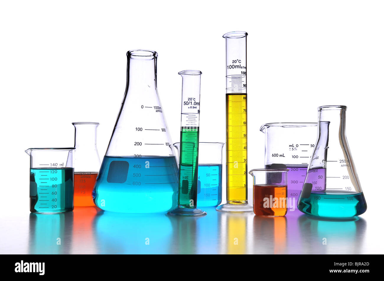 Laboratory glassware over white background with reflections on surface - Stock Image