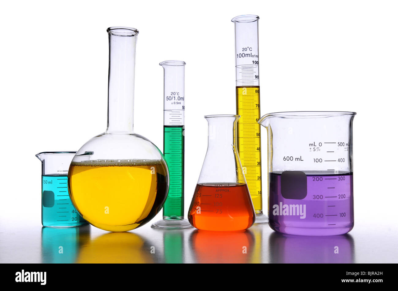 Laboratory glassware with liquids of different colors over white background - Stock Image